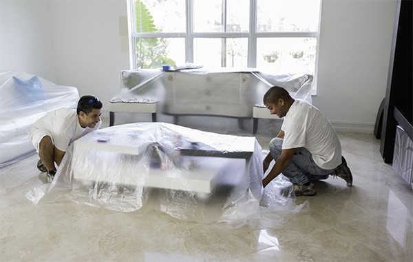 Painters covering furniture in preparation for painting interior walls